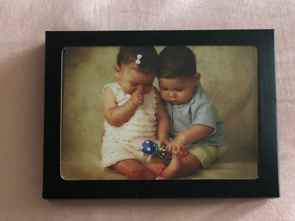 A photo of a baby boy and girl inside a black box with a frame lid